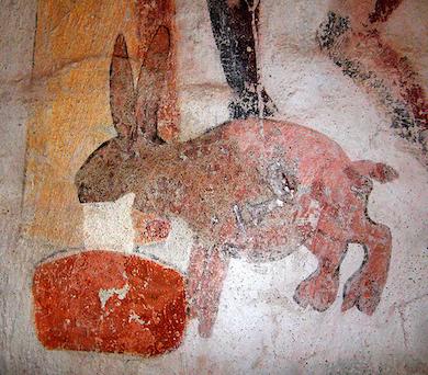 En bjära i form av en mjölkhare, som spyr upp mjölk  från grannens kor. Härkeberga kyrka 1400-talet.