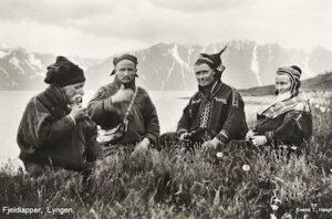 """Fjällsamer i Lyngen i Troms fylke 1928. Två av männen bär den för Kautokeinoområdet så typiska """"de fyra vindarnas mössa"""". Vykort publicerat av T. Høegh. (Wikimedia Commons)"""